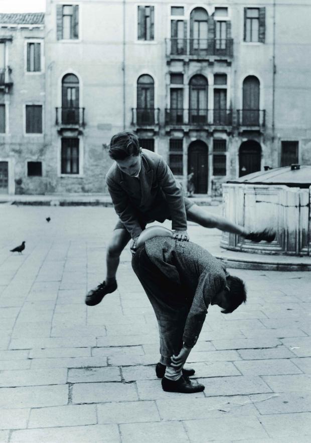 Due bambini giocano al salto della cavallina in campo San Barnaba a Venezia